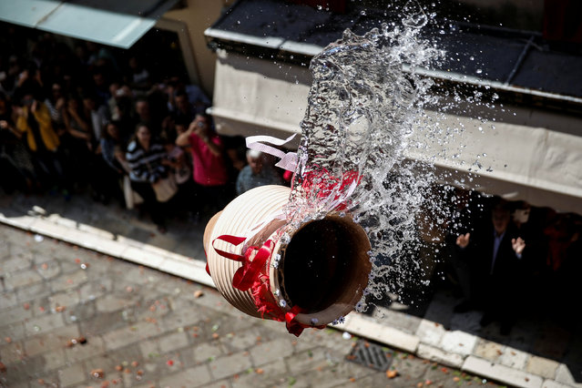 "A clay pot full of water is thrown from a balcony during the Greek Orthodox Easter tradition of ""Botides"" on Holy Saturday marking the so-called ""First Resurrection"", on the island of Corfu, Greece, April 30, 2016. (Photo by Alkis Konstantinidis/Reuters)"