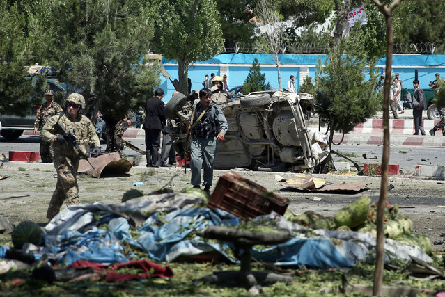 Afghan and NATO security forces work at the site of a suicide attack in Kabul, Afghanistan, Tuesday, June 30, 2015. (Photo by Massoud Hossaini/AP Photo)