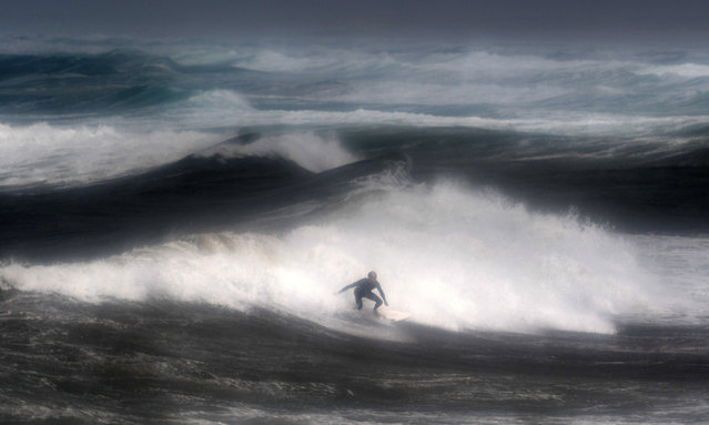 A man surfs a wave on August 9, 2019 at the Pointe-de-la-Torche in Plomeur, western France as strong winds hit the coast. (Photo by Fred Tanneau/AFP Photo)