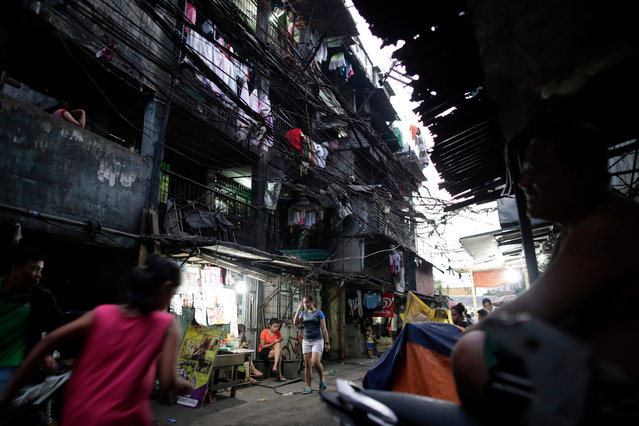 Filipino occupants are seen next to dilapidated buildings at a government housing project in Manila, Philippines, 12 March 2019 (issued 13 June 2019). (Photo by Francis R. Malasig/EPA/EFE)