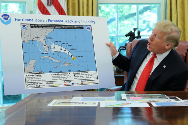 U.S. President Donald Trump holds a chart showing the original projected track of Hurricane Dorian that appears to have been extended with a black line to include parts of the Florida panhandle and of the state of Alabama during a status report meeting on the hurricane in the Oval Office of the White House in Washington, U.S., September 4, 2019. (Photo by Jonathan Ernst/Reuters)