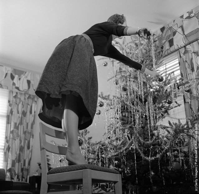 1955: When decorating a Christmas tree use a firm stepladder and don't be like this woman who is standing on a chair and leaning over too far