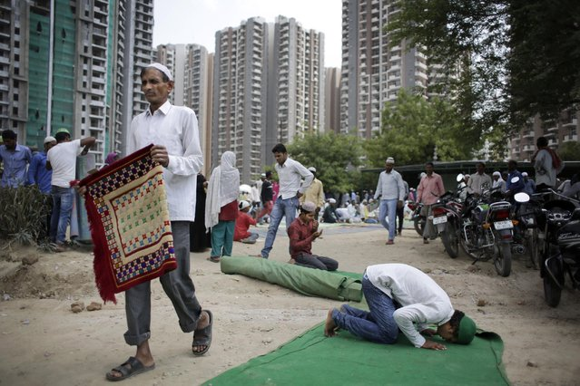 An Indian Muslim man prays as others leave after offering Ramadan prayers in the outskirts of New Delhi, India, Friday, July 3, 2015. (Photo by Altaf Qadri/AP Photo)