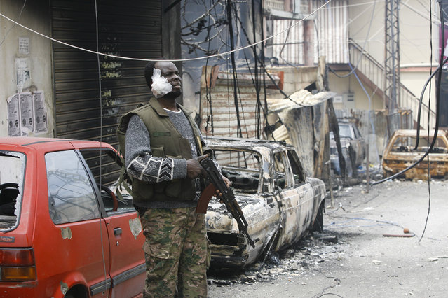 An injured member of the Palestinian Fateh Movement stands guard during a clashes that erupted between the Palestinian Fatah Movement and Islamists in the Palestinian refugee camp of Ein el-Hilweh near the southern port city of Sidon, Lebanon, Sunday, April 9, 2017. Ein el-Hilweh, the largest of 12 Palestinian refugee camps in Lebanon, is notorious for its lawlessness and is home to some extremists who sympathize with the Islamic State group and al-Qaida. (Photo by Mohammed Zaatari/AP Photo)