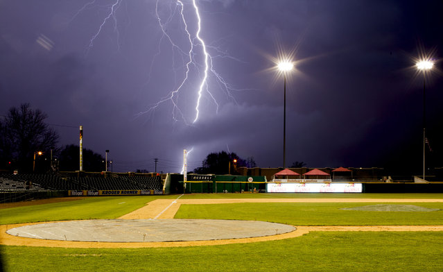 Lightning strikes in the distance as an exhibition game between the Bowling Green Hot Rods and the Western Kentucky Hilltoppers is rained out Tuesday, April 7, 2015, in Bowling Green, Ky. (Photo by Austin Anthony/AP Photo/Daily News)