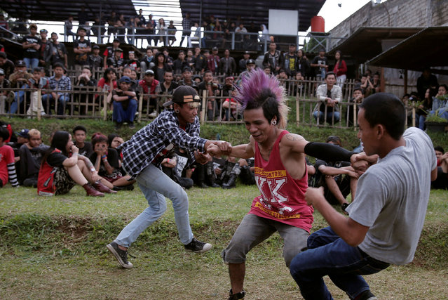 Punk community members dance during a punk music festival in Bandung, Indonesia West Java province, March 23, 2017. (Photo by Reuters/Beawiharta)