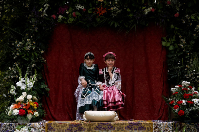 """Maya"" girl Ines de la Paloma, 9, (L), sits with her friend Nuria Sanchez Caballero, 6, at an altar during ""Las Mayas"" festivity in Madrid, Spain, May 8, 2016. ""Las Mayas"" festival is held annually at the beginning of May to celebrate the awakening of nature in Spring. Young girls are chosen to become ""Mayas"" and sit at altars decorated with flowers so that people can admire them. The ""Mayas"" are dressed in traditional costumes, often displaying shawls and a wreath of flowers on their heads. (Photo by Susana Vera/Reuters)"