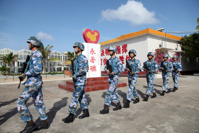 Soldiers of China's People's Liberation Army (PLA) Navy patrol at Fiery Cross Reef, in the Spratly Islands, known in China as the Nansha Islands, February 9, 2016. (Photo by Reuters/Stringer)