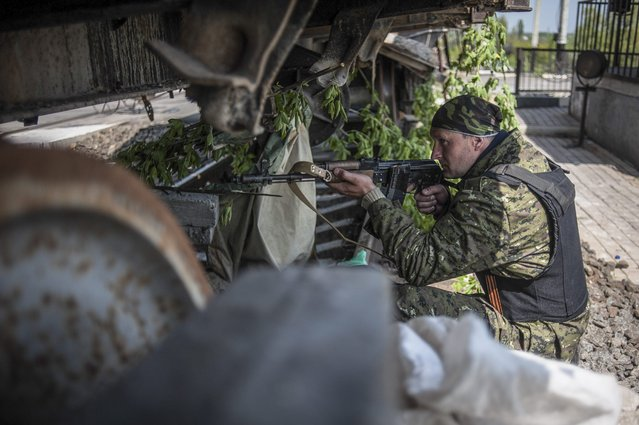 Armed pro-Russian militants stand guard at their checkpoint alongside a railway line in Slovyansk, on May 10, 2014. (Photo by Roman Pilipey/EPA)