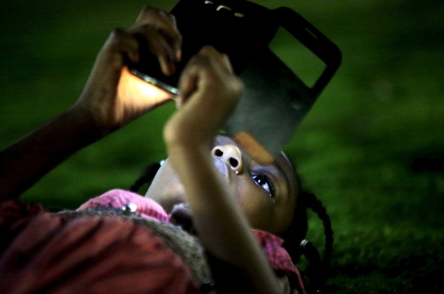 A girl uses her mobile phone during the evening at the National Park in Khartoum, Sudan, April 24, 2015. (Photo by Mohamed Nureldin Abdallah/Reuters)