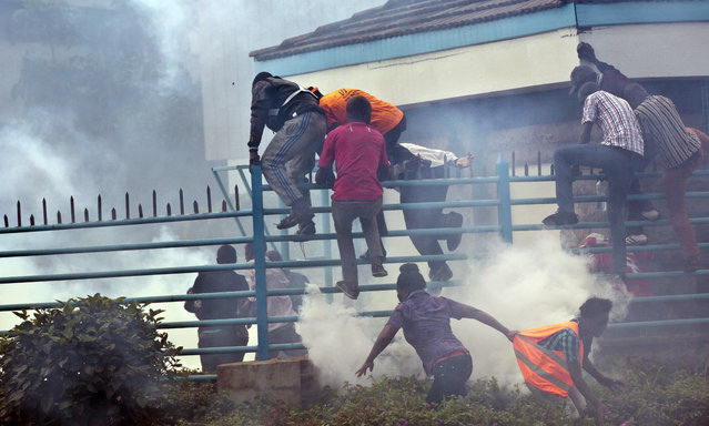 Opposition supporters climb over a fence into the University of Nairobi campus, as they flee from clouds of tear gas fired by riot police, during a protest in downtown Nairobi, Kenya Monday, May 16, 2016. (Photo by Ben Curtis/AP Photo)