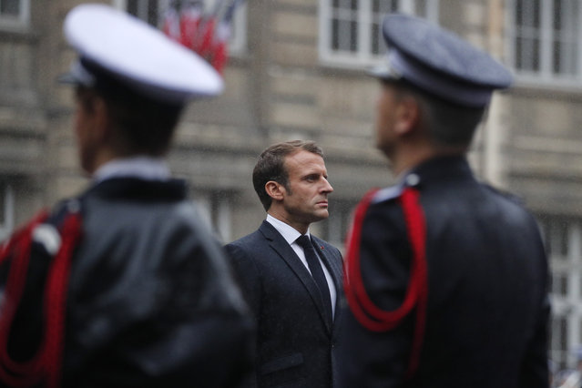 French President Emmanuel Macron stands at attention by the coffins of the four victims of last week's knife attack in the courtyard of the Paris police headquarters during a ceremony, Tuesday, October 8, 2019 in Paris. France's presidency says the four victims of last week's knife attack at the Paris police headquarters will be posthumously given France's highest award, the Legion of Honor. (Photo by Francois Mori/AP Photo/Pool)