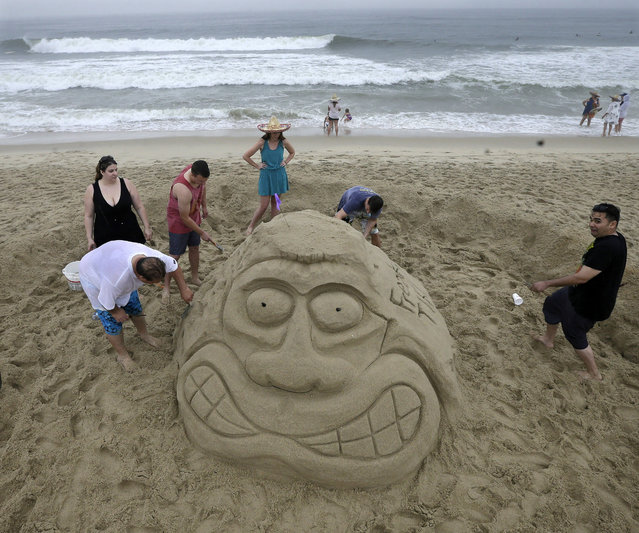 """People work in the rain on their sandcastles and sculptures during the """"NJ Sandcastle Contest"""", contest in Belmar, N.J., Wednesday, July 15, 2015. After nearby lightning strikes during a steady rain, the beach patrol stopped the competition and asked everyone to leave the beach. (Photo by Mel Evans/AP Photo)"""