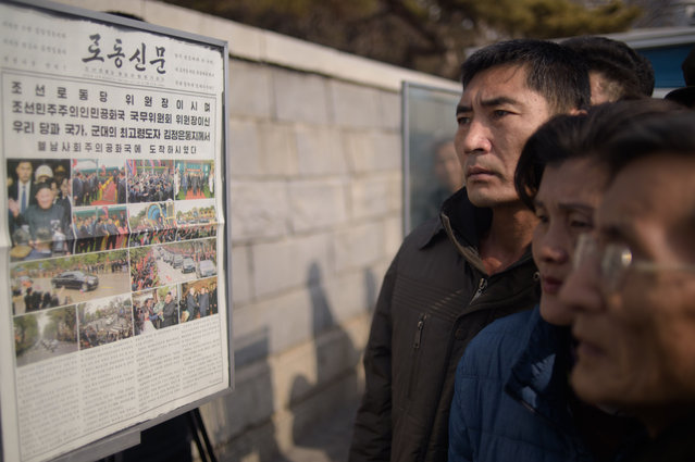 People read a copy of the Rodong Sinmun newspaper showing coverage of North Korea's leader Kim Jong Un arriving in Vietnam ahead of a Hanoi summit with US President Donald Trump, in Pyongyang on February 27, 2019. (Photo by Kim Won Jin/AFP Photo)