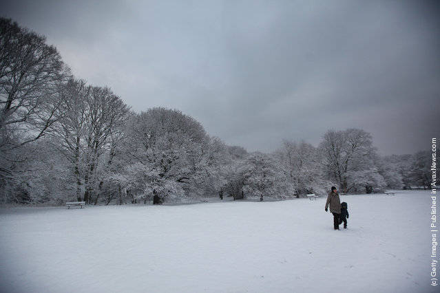 A woman walks with her child through the snow on Wimbledon common on February