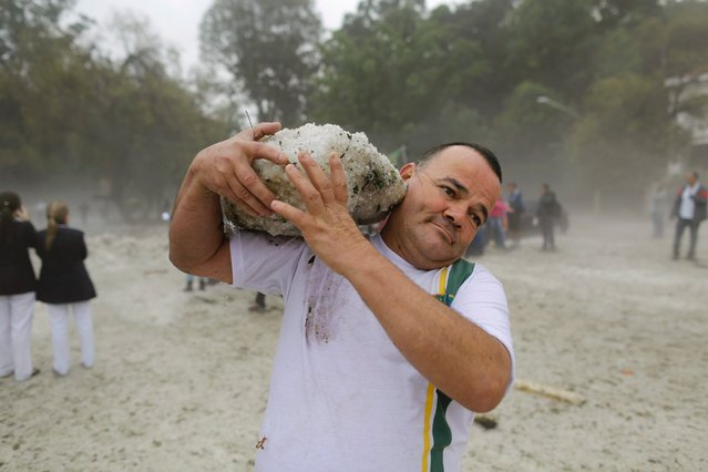 A man carries a block of ice left behind by a hailstorm in Sao Paulo, Brazil, on May 19, 2014. (Photo by Nelson Antoine/AP Photo)