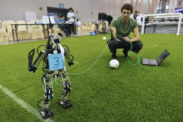 A participant tests a robot soccer player as he prepares for the upcoming RoboCup 2015, at an exhibition centre in Hefei, Anhui province, China, July 18, 2015. (Photo by Reuters/Stringer)
