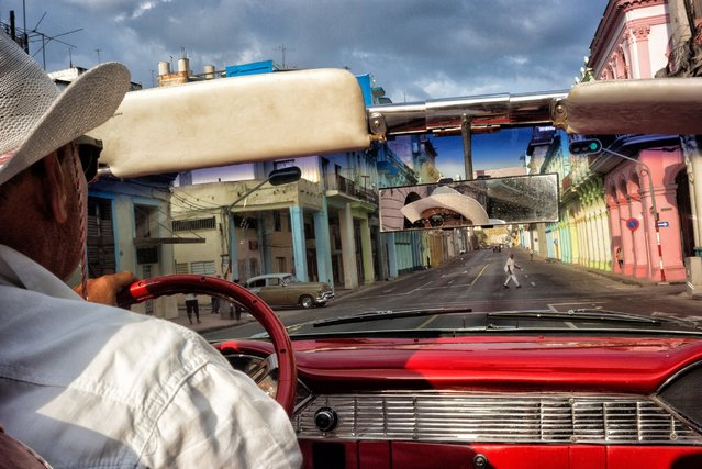 A 1955 Chevy Bel Air taxi driver cruises the colorful streets of Old Havana on the late afternoon of May 2, 2016. (Photo by Dotan Saguy)