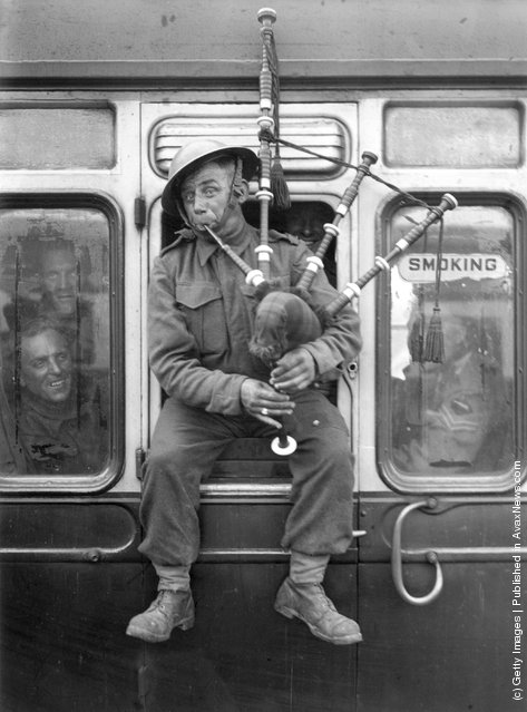 1940: Back in England, one of the British soldiers that continue to return in their thousands from Northern France, belies any mood of defeat with some high spirited piping on a train