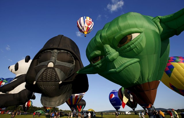 "Hot air balloons shaped as ""Star Wars"" characters Darth Vader (L) and Yoda (R) are inflated at sunrise on day one of the 2015 New Jersey Festival of Ballooning in Readington, New Jersey, July 24, 2015. (Photo by Mike Segar/Reuters)"