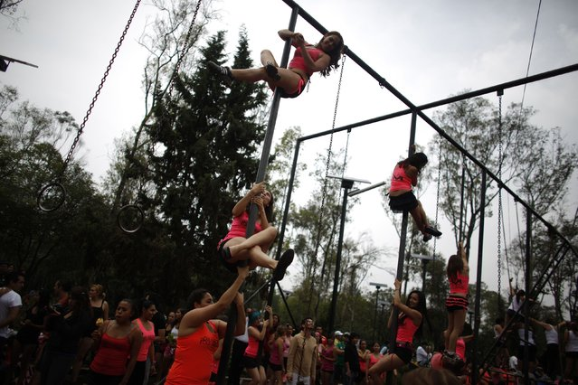 "Women perform a pole dancing routine during the national day celebration of ""Urban Pole"" dance at a park in Mexico City June 8, 2014. (Photo by Tomas Bravo/Reuters)"