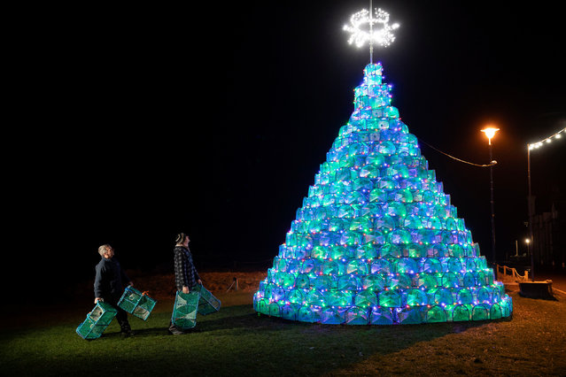Simon Eltingham (right) and Gordon Wink put the finishing touches to the 16ft Christmas tree that they have built on the harbour-side in Ullapool, Wester Ross, Scotland on November 28, 2019 which is created from 340 fishing creels used for catching prawns and crabs. (Photo by Jane Barlow/PA Images via Getty Images)