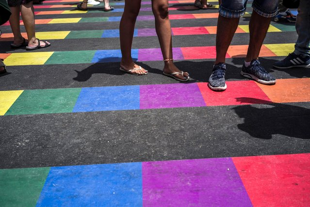People walk on a rainbow colored road as they take part in the annual Tel Aviv Gay Pride parade, June 3, 2016, in Tel Aviv. Thousands of people gathered in Tel Aviv for the parade, which attracts visitors from all over the world. (Photo by Ilia Yefimovich/Getty Images)