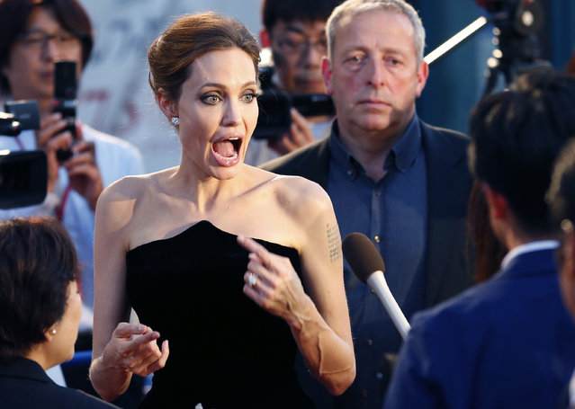 "Angelina Jolie reacts as she arrives at the Japan premiere of ""Maleficent"" in Tokyo Monday, June 23, 2014. (Photo by Shizuo Kambayashi/AP Photo)"