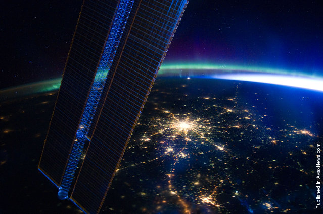 A well-lit Moscow and the aurora borealis, or Northern Lights, are seen from the perspective of the Expedition 30 crew aboard the International Space Station on March 28. A solar array panel for the space station is on the left side of the image