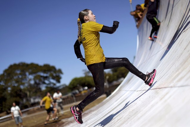 A woman runs up an obstacle during the Bravus Race competition in Brasilia, August 2, 2015. (Photo by Ueslei Marcelino/Reuters)