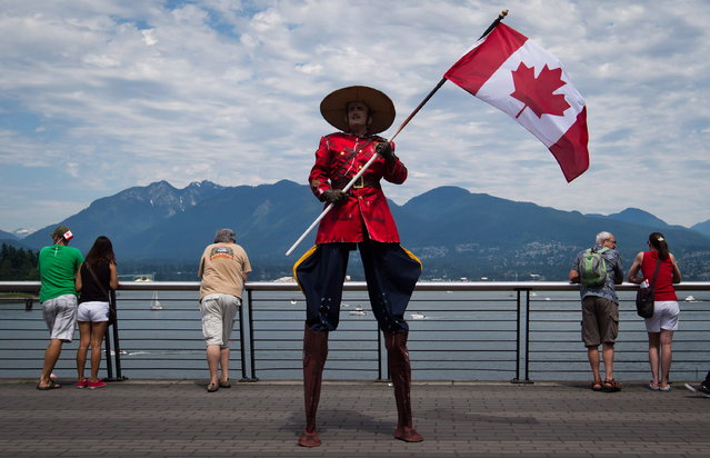 Dressed a Royal Canadian Mounted Police officer, Stephane Delage carries a Canadian flag while on stilts as he entertains the crowd during Canada Day festivities in Vancouver, B.C., on Monday, July 1, 2013. (Photo by Darryl Dyck/The Canadian Press)