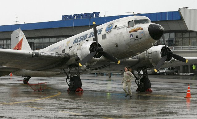 A Russian crew member runs past a U.S. Douglas C-47 Dakota military transport airplane constructed in the early 1940s, after landing during a transcontinental flight on the Alaska-Siberia route, at Yemelyanovo International Airport outside the Siberian city of Krasnoyarsk, Russia, August 4, 2015. (Photo by Ilya Naymushin/Reuters)