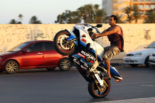 A Libyan man performs a wheelie on a road as youth gather to show-off their riding skills early on July 4, 2014, in the eastern city of Benghazi. (Photo by Abdullah Doma/AFP Photo)
