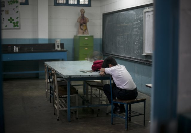 In this June 1, 2016 photo, a student lays his head down during class at a public high school in Caracas, Venezuela. The annual high school dropout rate has doubled to 11 percent since 2011 and schools are understaffed as professionals flee the country. (Photo by Ariana Cubillos/AP Photo)