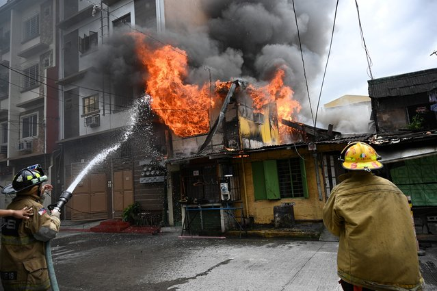 Firemen hose down a burning residence in Manila on November 1, 2019. (Photo by Ted Aljibe/AFP Photo)