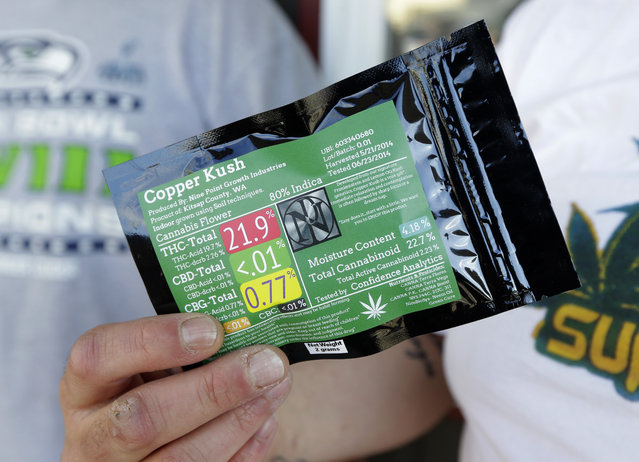 Julian Rodriguez, of Everson, Wash., holds his two-gram packet of recreational marijuana outside Top Shelf Cannabis, Tuesday, July 8, 2014, in Bellingham, Wash., on the first day of legal sales in the state. (Photo by Ted S. Warren/AP Photo)