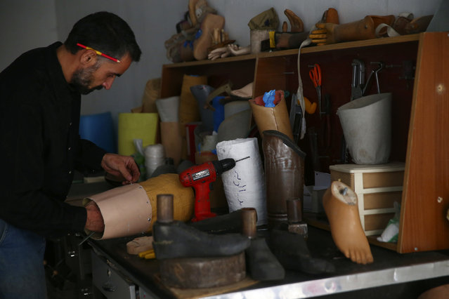 A worker works on prosthetic limbs at a welfare workshop in the Duma neighborhood in Damascus October 24, 2013. The center produces prosthesis from different materials including remnants of weapons, plastic mannequins and water barrels, and offer them to physically disabled victims of the war. (Photo by Bassam Khabieh/Reuters)