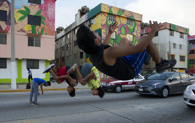In this June 30, 2017 photo, a group of boys who practice parkour do tricks at a traffic light to earn money from drivers, in Coatzacoalcos, Veracruz State, Mexico. The fresh wave of violence has touched regions of Mexico that were long seen as peaceful. (Photo by Rebecca Blackwell/AP Photo)
