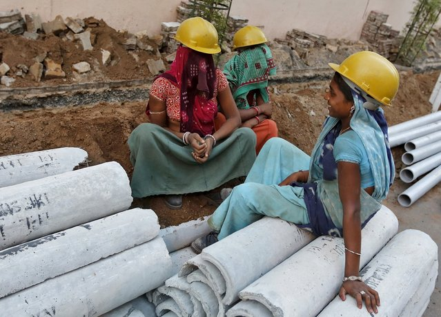 Female labourers wearing helmets take a break from laying underground electricity cables along a roadside in Ahmedabad, India, in this May 27, 2015 file photo. India is expected to release industrial output numbers for June this week. (Photo by Shailesh Andrade/Reuters)