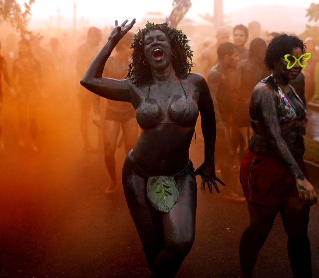 A woman dances amid orange smoke during the 'Bloco da Lama,' or Mud Block parade in Paraty