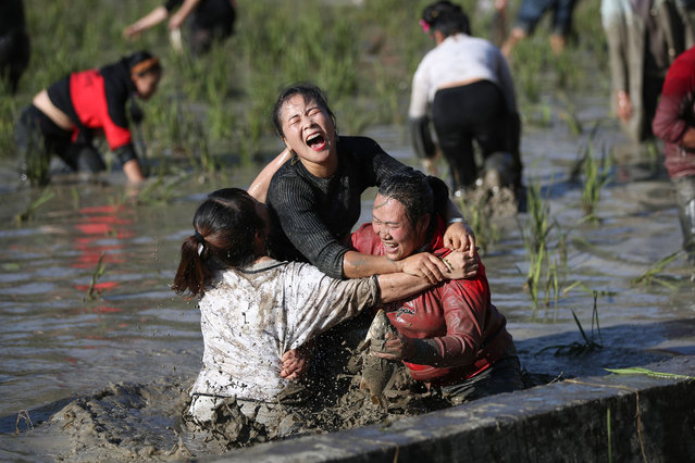 This photo taken on November 4, 2019 shows people taking part in a fish catching competition in a paddy field in Leishan county in China's southwestern Guizhou province, to celebrate the new year festival Miao people. (Photo by AFP Photo/China Stringer Network)
