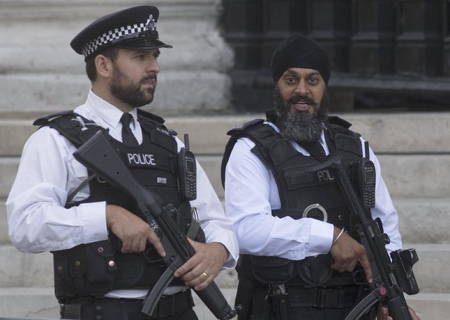 Armed police patrol St Martin's in the Fields church as members of the royal family and political leaders attend a service to commemorate the 70th anniverary of VJ Day, in London, Britain August 15, 2015. (Photo by Neil Hall/Reuters)