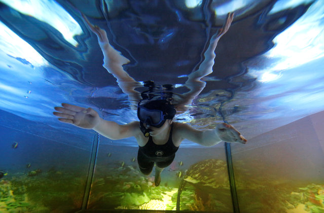 A woman demonstrates AquaCAVE, a system that augments swimming environment with immersive surrounded-screen VR to enhance the swimming experience, during an demonstration event organized by Sony Corp.'s human augmentation research project with the University of Tokyo, in Tokyo, Japan, March 13, 2017. (Photo by Issei Kato/Reuters)