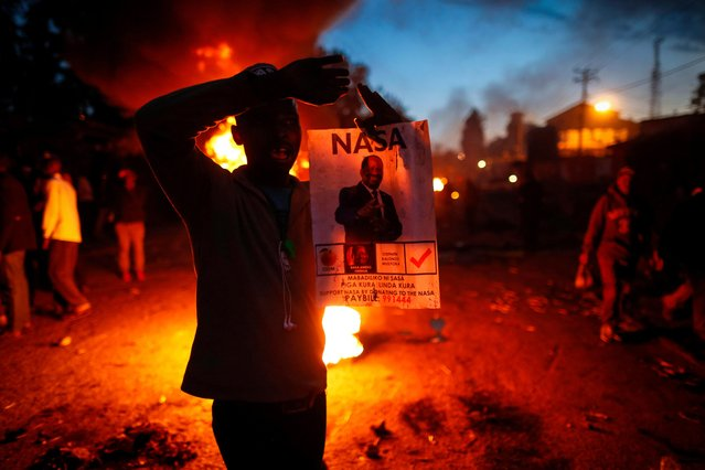 A supporter of the opposition coalition The National Super Alliance (NASA) and its leader Raila Odinga reacts in front of a burning tire during a protest after Odinga announced that he rejects the provisional result of the presidential election announced by the electoral body, in Kibera slum, one of Odinga's strongholds in Nairobi, Kenya, 09 August 2017. Provisional result of the presidential poll shows incumbent Uhuru Kenyatta leading opposition leader Raila Odinga, who rejected them saying that the official tally doesn't match their own counts. The police is beefing up security on Nairobi streets as the fear of the post-election violence looms. (Photo by Dai Kurokawa/EPA)