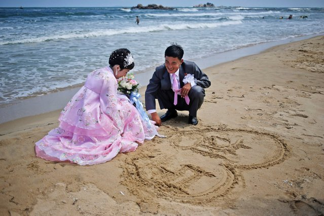 A newlywed couple draws a heart shape in the sand during a photo shoot on Sijung Ho beach in North Korea, August 18, 2015. The couple gathered with their friends and family members to have their pictures taken after their wedding ceremony. (Photo by Dita Alangkara/AP Photo)