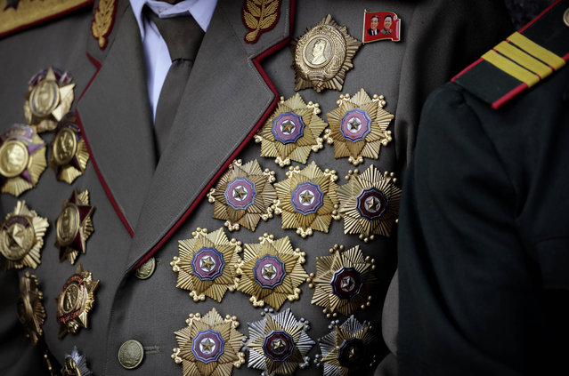 A North Korean war veteran is decorated with medals as he attends a parade to celebrate the anniversary of the Korean War armistice agreement, Sunday, July 27, 2014 in Pyongyang, North Korea. North Koreans gathered at Kim Il Sung Square as part of celebrations for the 61st anniversary of the armistice that ended the Korean War. (Photo by Wong Maye-E/AP Photo)