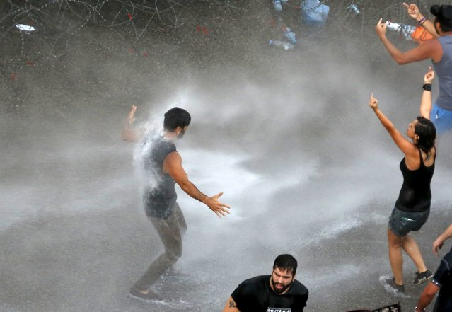 Lebanese protesters are sprayed with water during a protest against corruption and rubbish collection problems near the government palace in Beirut August 22, 2015. (Photo by Jamal Saidi/Reuters)