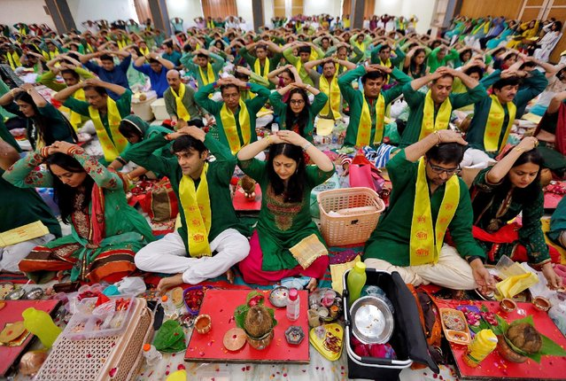 """Hindu devotees put their hands on their heads as they pray to seek blessings from their spiritual leader during the annual festival of """"Guru Purnima"""" inside an ashram in Ahmedabad, India, July 19, 2016. (Photo by Amit Dave/Reuters)"""