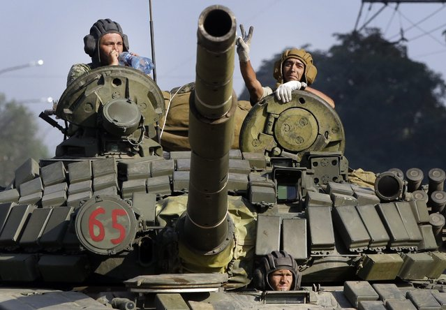 Pro-Russian rebels ride on a tank in the town of Krasnodon, eastern Ukraine, Sunday, August 17, 2014. A column of several dozen heavy vehicles, including tanks and at least one rocket launcher, rolling through rebel-held territory on Sunday. (Photo by Sergei Grits/AP Photo)