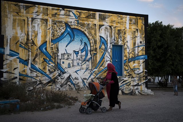 """A woman, pushing a stroller, looks at a mural by French artist KATRE in the village of Erriadh, on the Tunisian island of Djerba, on August 7, 2014, as part of the artistic project """"Djerbahood"""". (Photo by Joel Saget/AFP Photo)"""